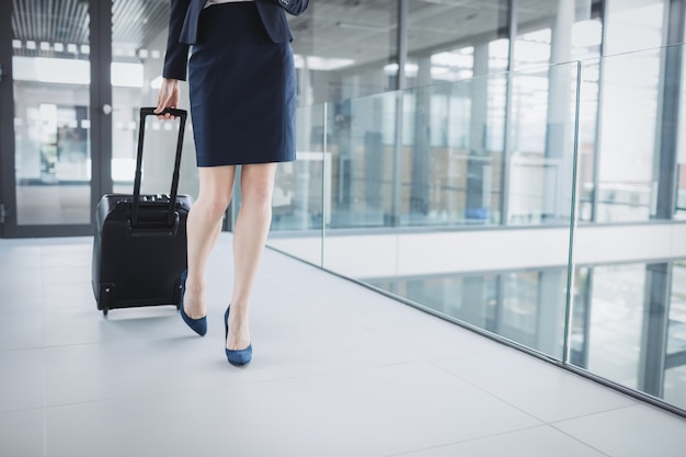 Businesswoman holding suitcase walking through office