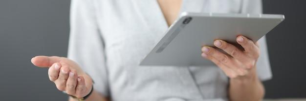 Деловая женщина держит планшет в руках и машет рукой в концепции бизнес-образования офиса