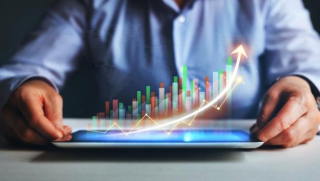統計グラフとチャートの仮想ホログラムが成長しているタブレットを保持している実業家