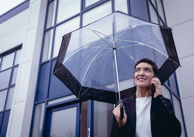 Businesswoman holding umbrella while talking on mobile phone