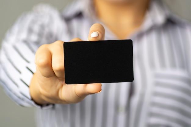 Деловая женщина держит в руке черную визитную карточку.