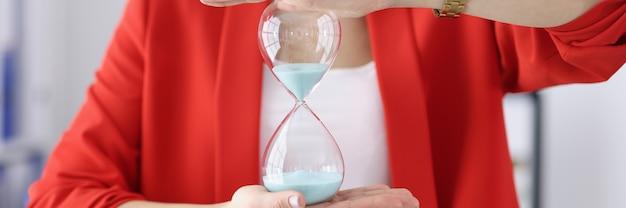 Деловая женщина держит в руках песочные часы