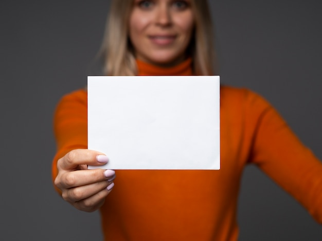 Businesswoman holds blank card mockup with space for text on a grey background.