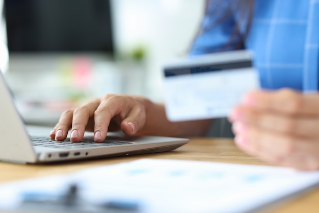 実業家はクレジットプラスチックカードを保持し、ラップトップキーボードのオンライン支払いで番号をダイヤルします