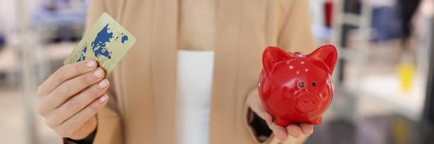 実業家は彼女の手にクレジットプラスチックの銀行カードと赤豚の貯金箱を持っています