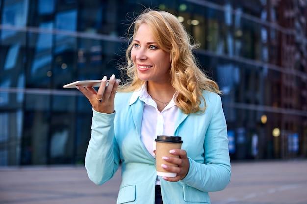 実業家は彼女の手でコーヒーの紙コップを保持し、電話で話します