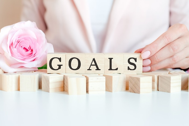 A businesswoman holds a wooden cube with the text of goals in her hand. on the wooden cubes there is a living rose flower. pink wall, front view. business and economic concept
