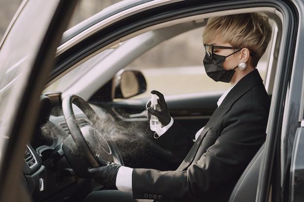 Деловая женщина в черной маске сидит в машине