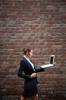 Businesswoman in a brick wall background