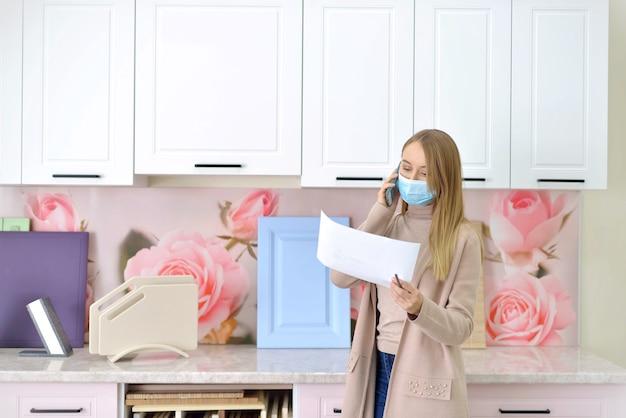 Деловая женщина в маске утверждает проект корпусной мебели удаленно во время пандемии, разговаривая по смартфону.