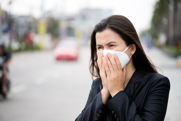 Деловая женщина в костюме носить защитную маску и кашель