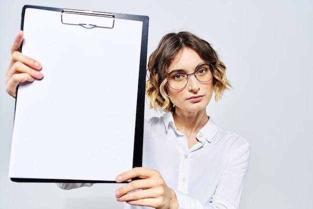 白いシャツと分離された空のクリップボードを保持しているメガネの女性実業家