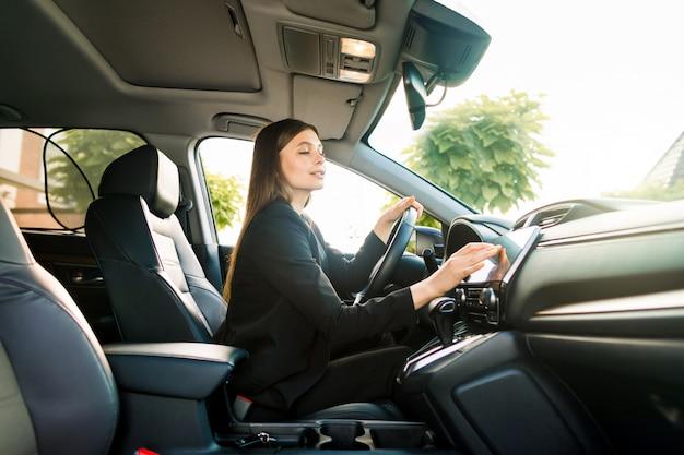 黒いスーツの女性実業家が高級車のホイールの後ろに座って、ナビゲーションシステムのモニターを見る方法を見る