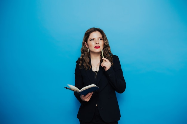 赤い唇と巻き毛のメモ帳を保持し、青い壁で考えている黒いスーツの実業家