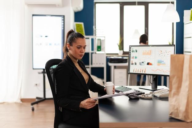 Деловая женщина в корпоративном запуске офиса анализа документов, диаграммы, смотрящей в буфер обмена. переработанный бумажный пакет с вкусной вкусной едой на обеденный перерыв. сотрудник, держащий чашку кофе.