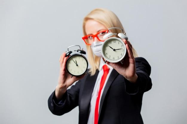 Деловая женщина в маске и красные очки с будильником