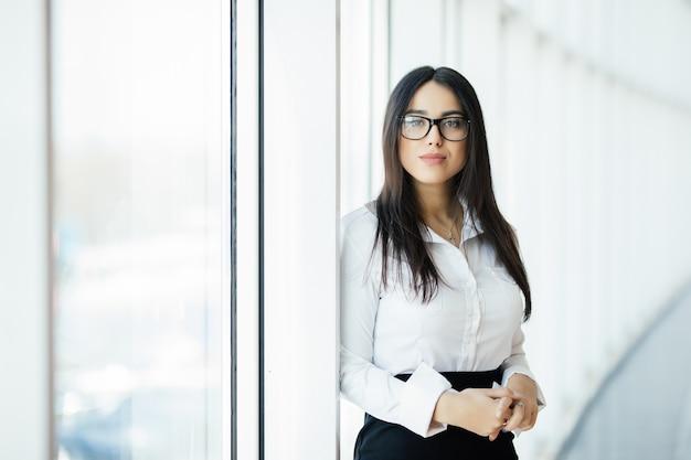 Деловая женщина в очках скрещенными руками портрет в офисе с панорамными окнами. бизнес-концепция