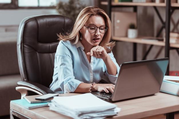 Деловая женщина в очках. трудолюбивая красивая бизнесвумен в очках читает рабочую электронную почту