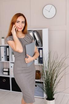 オフィスで紙のフォルダーと灰色のドレスの実業家
