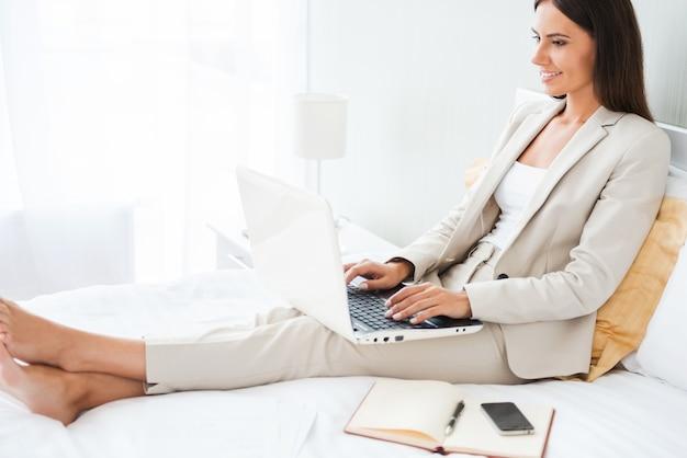 Деловая женщина в гостиничном номере. красивая молодая деловая женщина в костюме работает на ноутбуке и улыбается, сидя в постели в гостиничном номере