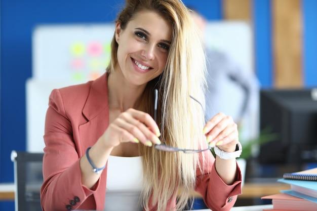 オフィスの女性実業家はテーブルに座って、彼女の手と笑顔でメガネを保持しています。ビジネスおよび経営コンサルティングのコンセプト