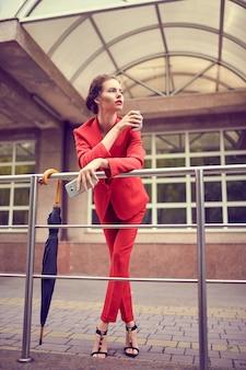 Деловая женщина в красном костюме с помощью мобильного телефона возле современного здания.