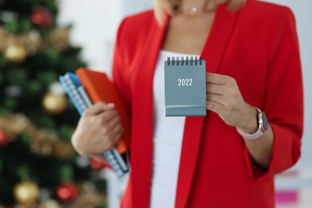 Деловая женщина в красной куртке держит календарь на 2022 год на фоне новогодней елки. бизнес-планирование в концепции 2022 года