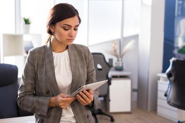 Деловая женщина в офисе, глядя на планшет