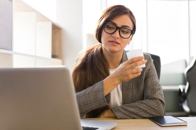 Деловая женщина в офисе, работающем на ноутбуке