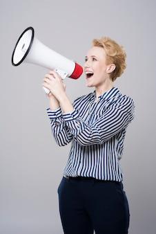 Деловая женщина в студии с помощью мегафона