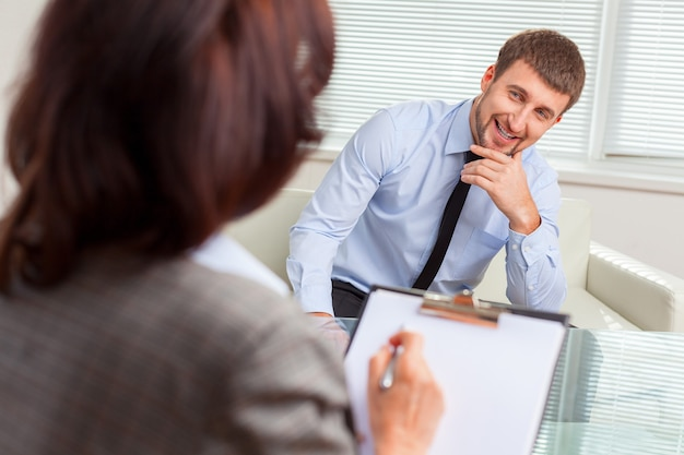 Businesswoman interviewing job applicant on background