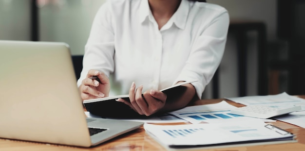 Businesswoman investment consultant analyzing company annual financial report balance statement working with documents graphics.