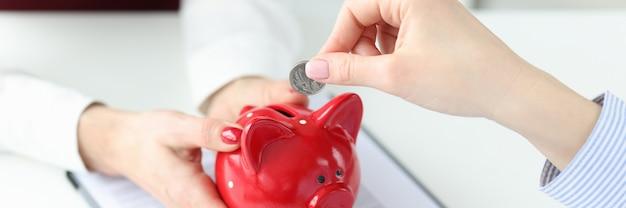 여성 사업가가 빨간 돼지 저금통을 들고 있으며 초기 자본 축적에 동전을 넣습니다.