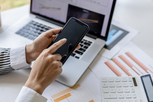 A businesswoman is holding a smartphone and using it, she is using a smartphone to send text messages to a company partner about financial statements. concept of using technology in communication.