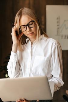 実業家は仕事でいっぱいで、コンピューターで働く頭痛、職場でのストレスを抱えています。