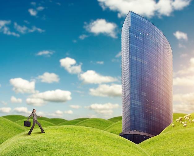 実業家は草の丘の上の建物に走っています