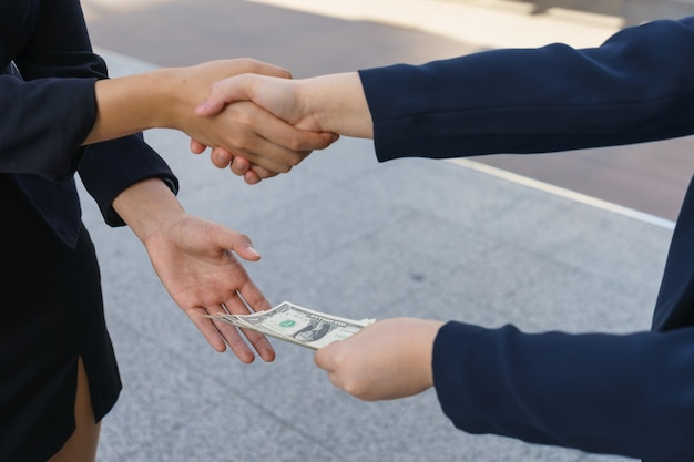 Businesswoman is shaking hand while other hand receives money for bribery.