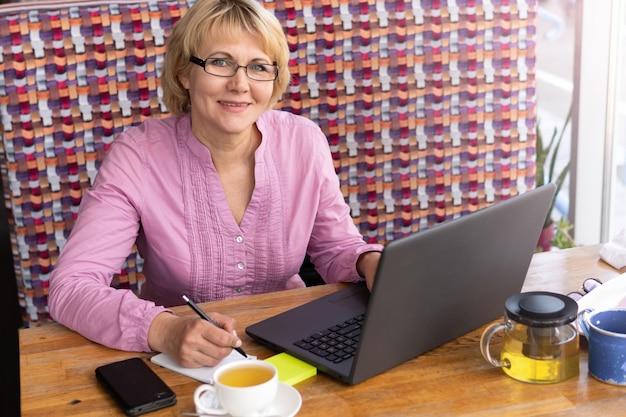 Деловая женщина сидит за столом перед ноутбуком. образование для взрослых. пенсионер-фрилансер работает. женщина болтает, ведет блог, проверяет электронную почту. социальные сети, сети.