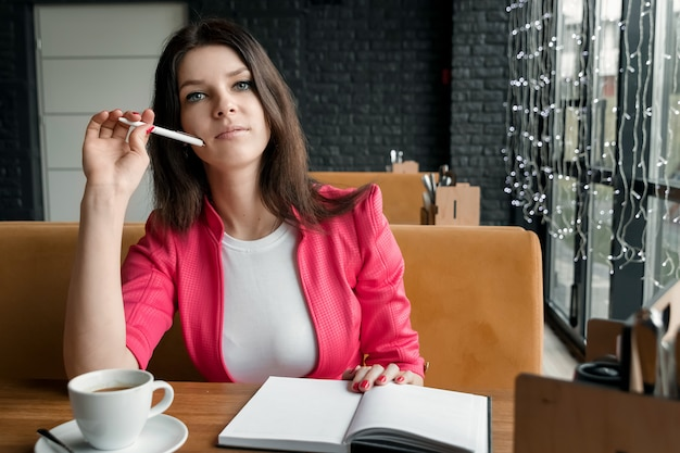 Businesswoman is sitting in a cafe thinking about something