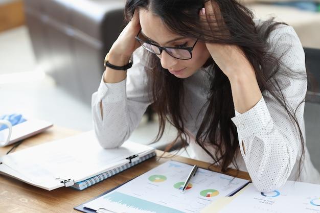 Деловая женщина сидит в офисе со столом, держа ее за голову руками