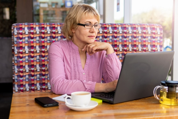 Businesswoman is sitting at table in front of laptop . education for adults. pensioner freelancer works. woman is chatting, blogging, checking email. social media, network.