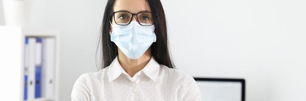 사업가 보호 의료 마스크를 착용하는 사무실에 서있다. 코로나 바이러스 전염병 개념에서 일하십시오.