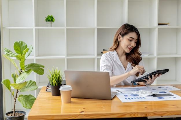 Деловая женщина использует планшет для поиска информации и общения в чате, она является владельцем бизнеса, она направляет сотрудников через планшетный мессенджер. концепция азиатской бизнес-леди и использование технологий.