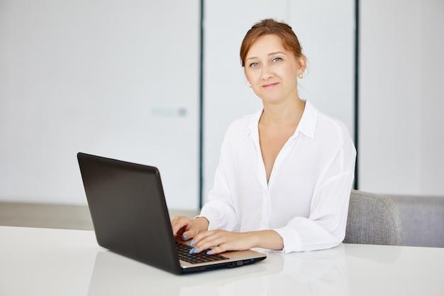 実業家は自宅で仕事にラップトップを使用しています女性はノートブックを持ってオフィスに座っています