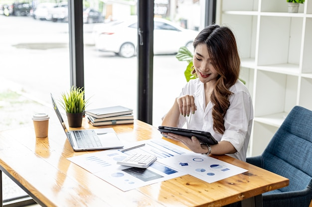 Businesswoman is using a tablet to search for information and chat, she is a business owner, she is directing employees through a tablet messenger. asian business woman concept and use of technology.