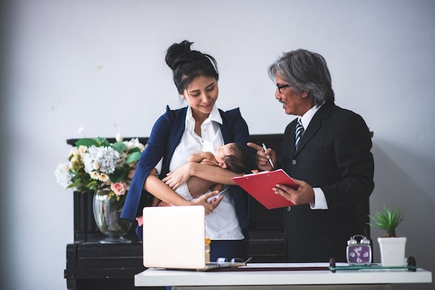 Businesswoman is working by holding her baby