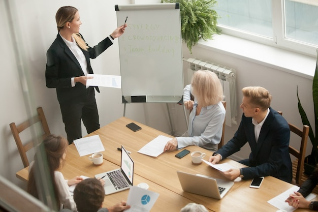 Businesswoman leader giving presentation explaining team goals at group meeting