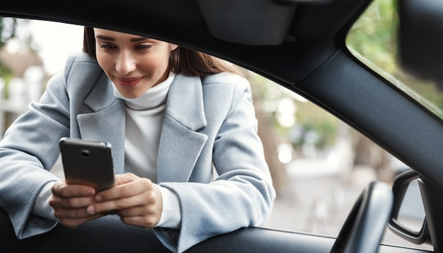 Businesswoman leaning on car window and texting message on phone, smiling happy.