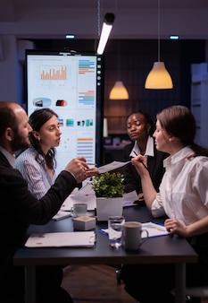 재무 그래프 서류에 대해 논의하는 마케팅 프레젠테이션을 분석하는 책상에 앉아 있는 사업가입니다. 늦은 밤 회의실에서 일하는 다양한 다민족 팀워크 브레인스토밍 프로젝트 아이디어