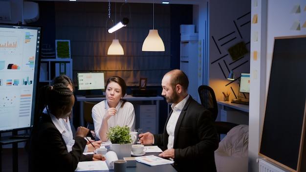 재무 문제에 대해 논의하는 마케팅 프레젠테이션을 분석하는 책상에 앉아 있는 사업가